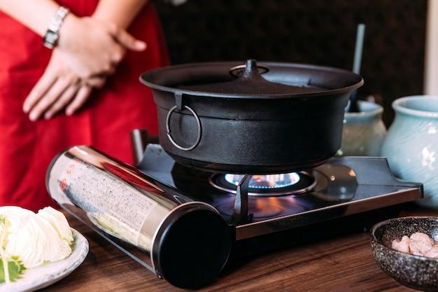 Um quimono vestindo da mulher está esperando o potenciômetro quente da cor preta de sukiyaki que ferve.