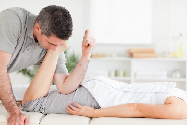 Um quiroprático alonga a perna de um cliente