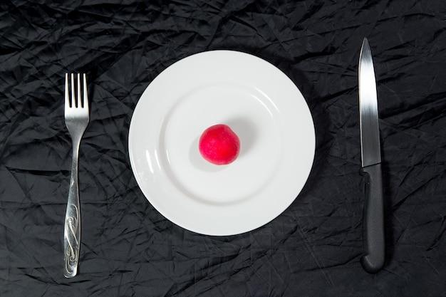 Um rabanete vermelho na chapa branca sobre fundo preto com garfo e faca. vista do topo
