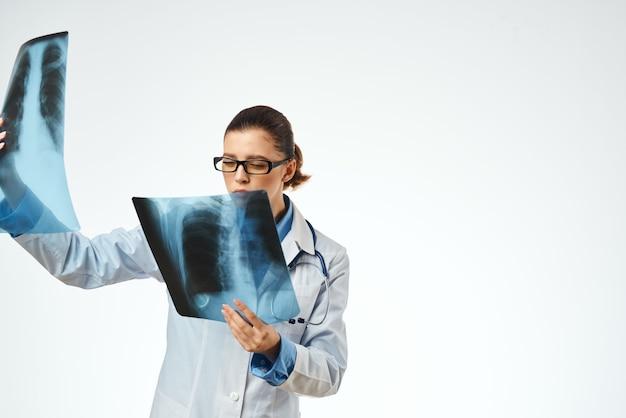 Um radiologista de jaleco branco examina radiografias tratando um paciente