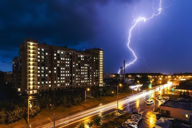 Um raio durante uma tempestade no contexto de um edifício da cidade. tráfego da cidade à noite.