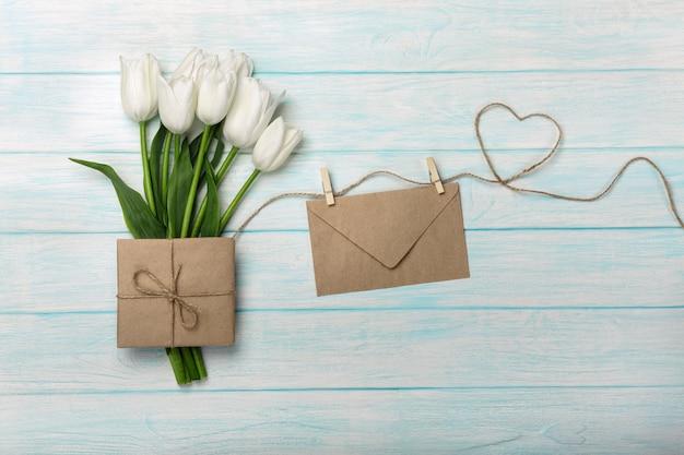 Um ramalhete das tulipas brancas com uma nota e um envelope do amor em uma corda coração-dada forma e em placas de madeira azuis. dia das mães