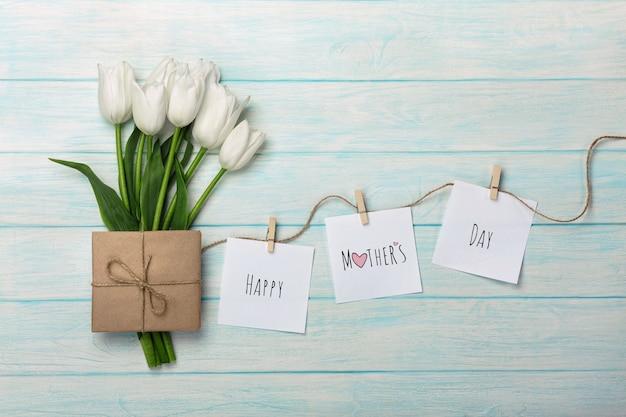 Um ramalhete das tulipas brancas e do envelope com etiquetas com pregadores de roupa em uma corda e em placas de madeira azuis. dia das mães