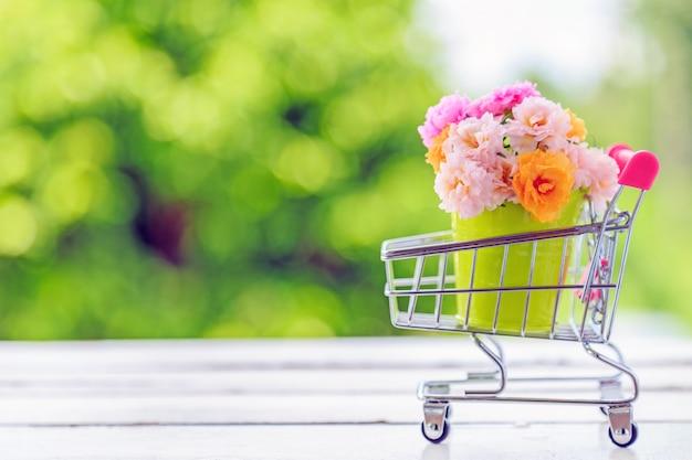 Um ramalhete de flores cor-de-rosa do musgo em uma mini cubeta verde no assoalho de madeira.