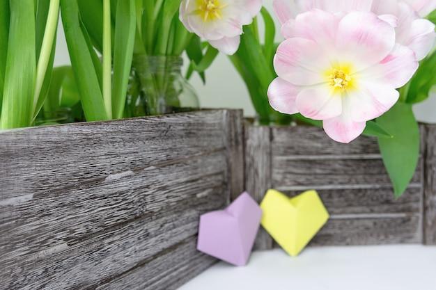 Um ramalhete de tulipas cor-de-rosa em uma caixa de madeira e dois corações de papel da cor amarela e lilás em um fundo branco.
