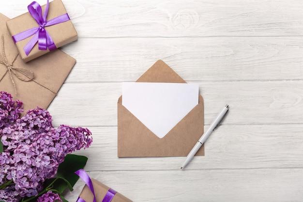 Um ramalhete dos lilacs com envelope do ofício, caixa de presente, uma nota do amor nas placas brancas. dia das mães