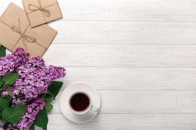 Um ramalhete dos lilacs com o copo de envelopes do chá e do ofício nas placas brancas. dia das mães