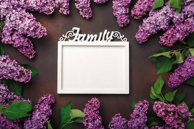 Um ramalhete dos lilacs com um frame branco para a inscrição no fundo oxidado. dia das mães