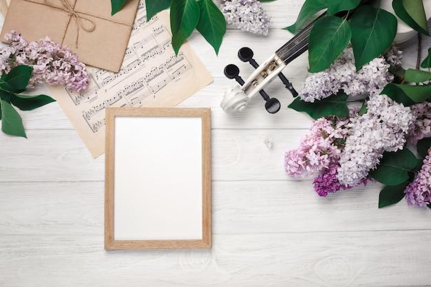 Um ramalhete dos lilacs com violino, placa de giz e folha de música em uma tabela de madeira branca. top wiev com espaço para o seu texto