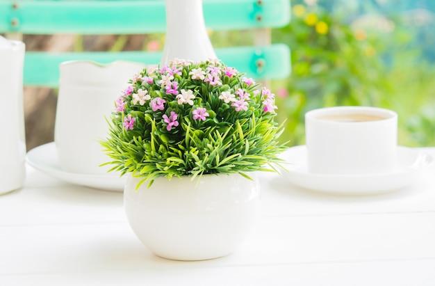 Um ramalhete plástico da flor em um vaso esférico branco em uma refeição da manhã.
