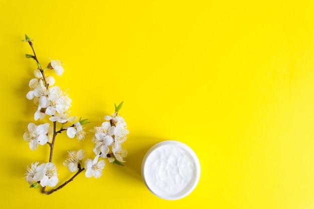 Um raminho de cereja florescendo em um fundo amarelo e um pote de creme para cuidados com a pele