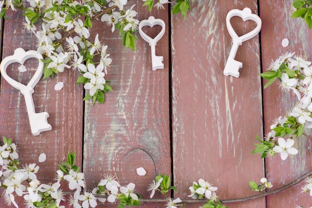 Um ramo de cerejeira em flor e três chaves decorativas de madeira