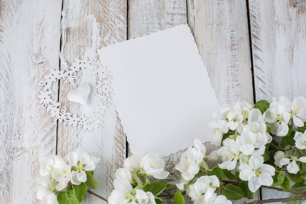 Um ramo de uma macieira florescendo, uma folha de papel e um coração de rendilhado
