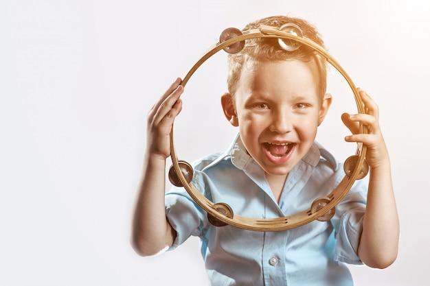 Um rapaz alegre de camisa azul, segurando um pandeiro e sorrindo