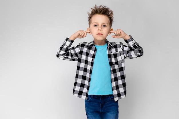 Um rapaz bonito em uma camisa xadrez, camisa azul e calça jeans