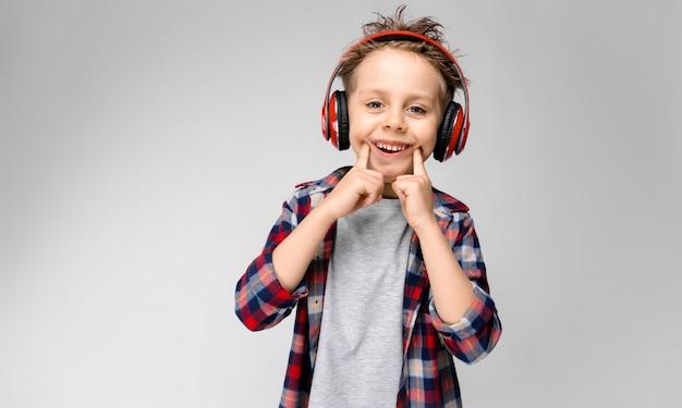 Um rapaz bonito em uma camisa xadrez, camisa cinza e calça jeans fica em um fundo cinza. um garoto em fones de ouvido vermelhos. o garoto estica os dedos com um sorriso.