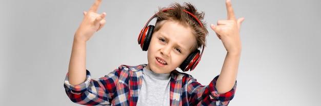 Um rapaz bonito em uma camisa xadrez, camisa cinza e calça jeans fica em um fundo cinza. um menino em fones de ouvido vermelhos mostra uma cabra de balancim.