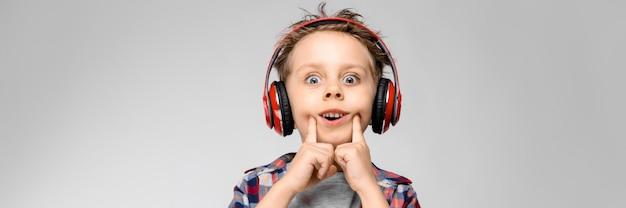 Um rapaz bonito em uma camisa xadrez, camisa cinza e calça jeans fica em uma parede cinza com fones de ouvido vermelhos.