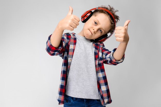 Um rapaz bonito em uma camisa xadrez, camisa cinza e calça jeans fica em uma parede cinza com fones de ouvido