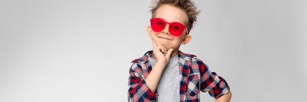 Um rapaz bonito em uma camisa xadrez, camisa cinza e calça jeans fica. um garoto de óculos vermelhos. o garoto apoiou o queixo com dois dedos