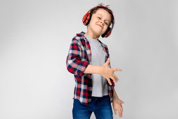 Um rapaz bonito em uma camisa xadrez, camisa cinza e jeans fica em cinza