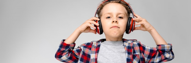 Um rapaz bonito em uma camisa xadrez e fones de ouvido
