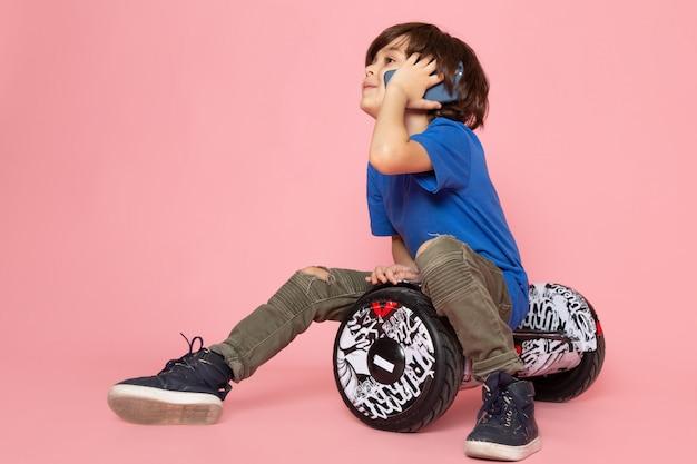 Um rapaz bonito vista frontal em camiseta azul falando ao telefone e sentado no espaço rosa segway
