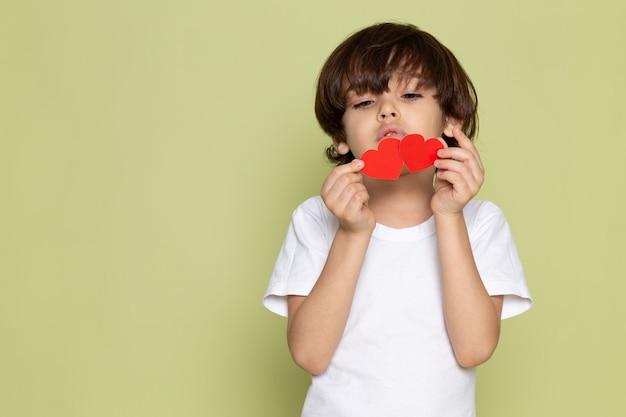 Um rapaz bonito vista frontal em t-shirt branca e segurando figuras de coração no espaço colorido de pedra