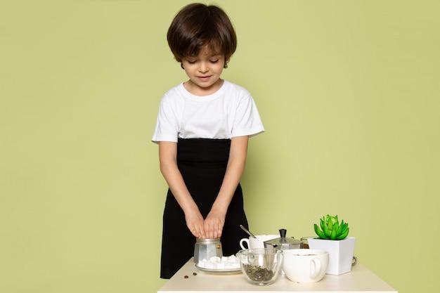 Um rapaz bonito vista frontal em t-shirt branca, preparando a bebida de café no espaço colorido de pedra