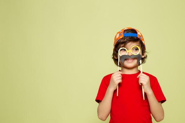 Um rapaz bonito vista frontal em t-shirt vermelha e boné de beisebol no espaço colorido de pedra