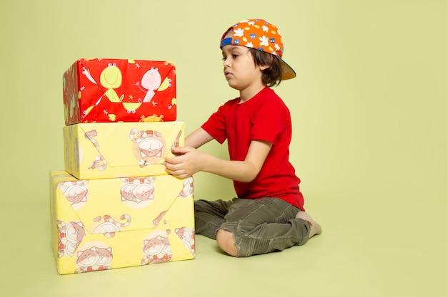 Um rapaz bonito vista frontal em t-shirt vermelha preparando presentes no espaço colorido de pedra