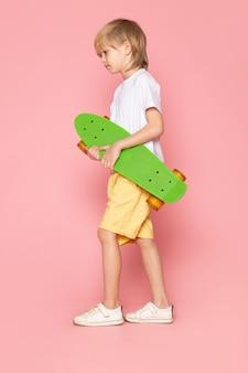 Um rapaz de cabelos loiros de vista frontal em camiseta branca e calça jeans amarela segurando o skate verde no espaço rosa