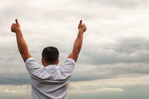 Um rapaz de camiseta branca no lago. polegar para cima. liberdade. pôr do sol na água.