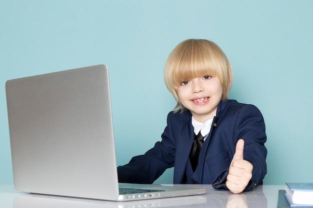 Um rapaz de negócios bonito vista frontal no terno clássico azul posando na frente do laptop prata trabalhando sorrindo negócios trabalho moda