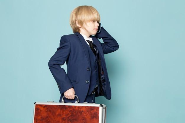 Um rapaz de negócios bonito vista frontal no terno clássico azul posando segurando segurando a mala marrom-prata, falando ao telefone