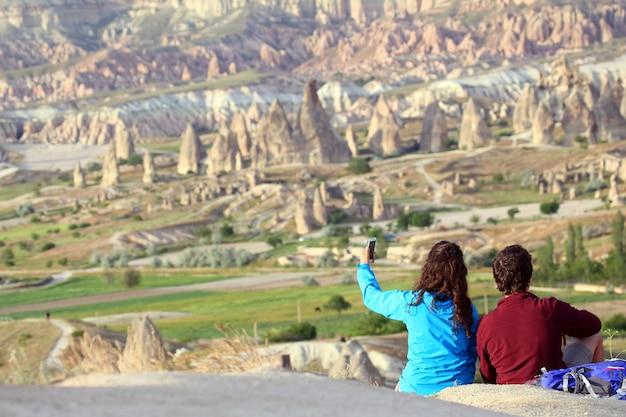 Um rapaz e uma garota fazendo uma selfie com colinas de rocha vulcânica no vale da capadócia, na turquia