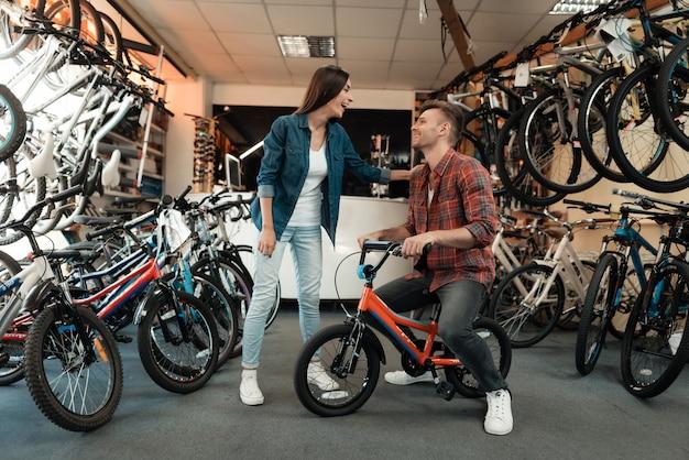 Um rapaz e uma menina estão escolhendo uma bicicleta infantil.