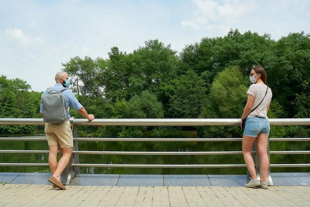 Um rapaz e uma rapariga com máscaras faciais descansando encostado na cerca no passeio.