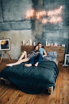 Um rapaz e uma rapariga deitam-se na cama do quarto a olharem um para o outro