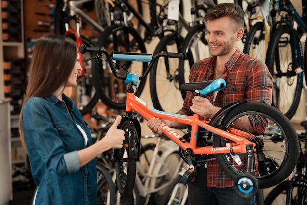 Um rapaz e uma rapariga estão a escolher uma bicicleta para crianças