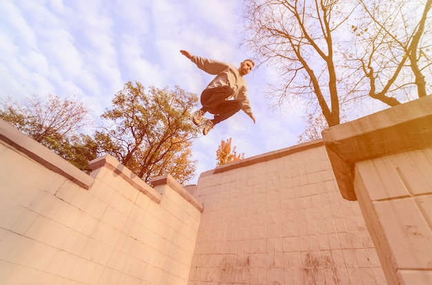 Um rapaz executa um salto no espaço entre edifícios