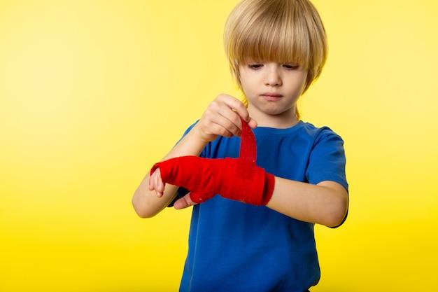 Um rapaz loiro vista frontal bonito em t-shirt azul e tecido vermelho em torno de sua mão na parede amarela