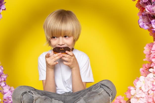 Um rapaz loiro vista frontal comendo rosquinhas em camiseta branca no chão amarelo