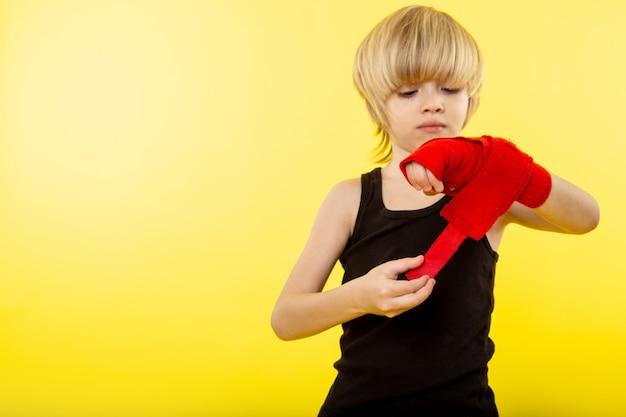 Um rapaz loiro vista frontal em camiseta preta e tecido vermelho em volta da mão na parede amarela