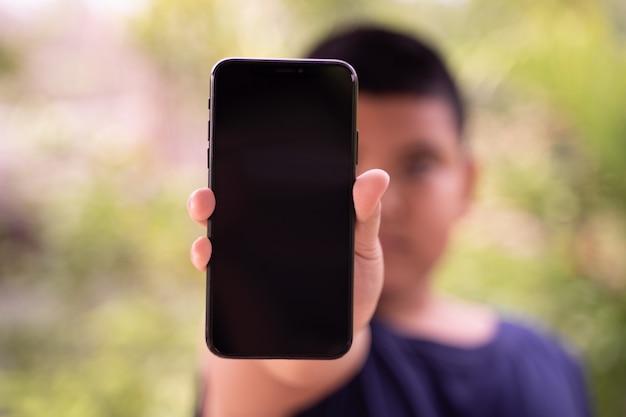 Um rapaz mostrando smartphone de tela preta em branco na mão