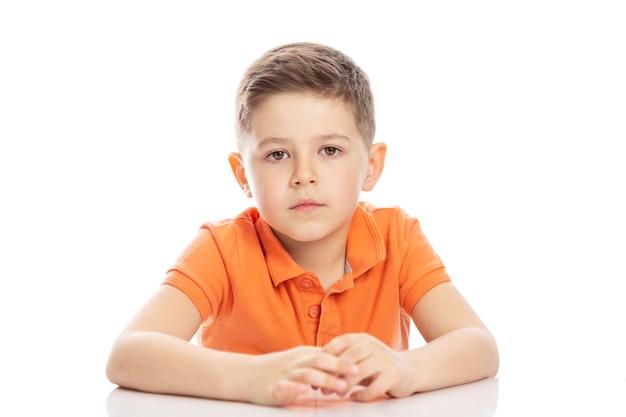 Um rapaz sério em idade escolar, vestindo uma camiseta polo laranja brilhante, está sentado à mesa. isolirvoan em um fundo branco.