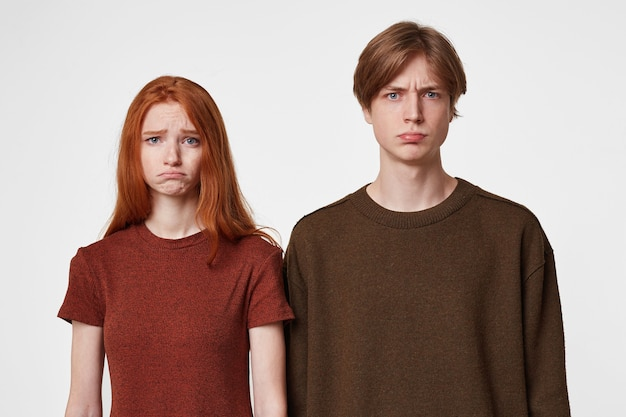 Um rapazinho zangado e chateado e uma rapariga ruiva isolada no branco