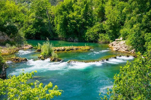 Um rápido rio de montanha corre pelas corredeiras
