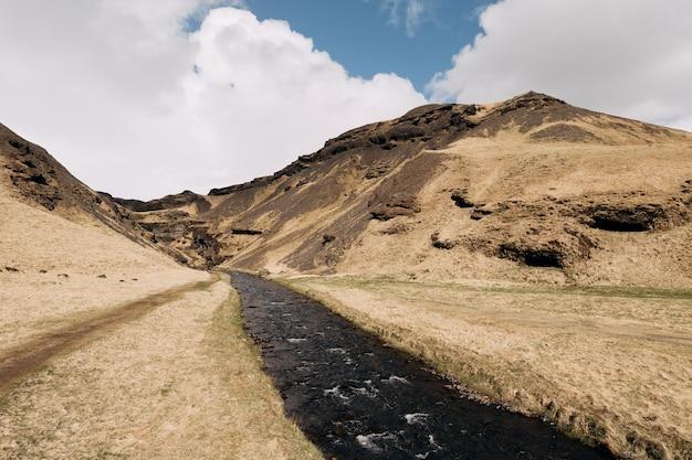 Um rápido rio de montanha flui entre um campo de grama seca e amarela em um cenário de pequenas montanhas