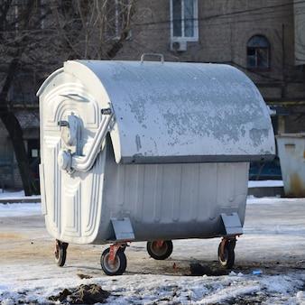 Um recipiente de lixo de prata fica perto de edifícios residenciais no inverno